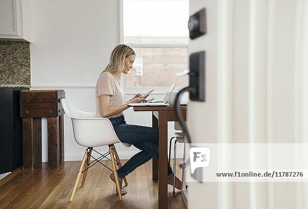 Volle Seitenansicht der mittleren erwachsenen Frau  die das Handy hält  während sie zu Hause den Laptop benutzt.