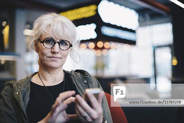 Portrait of confident mature businesswoman using mobile phone in office