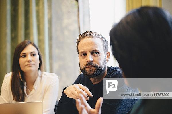 Zuversichtlicher Geschäftsmann  der während der Vorstandssitzung auf weibliche Kollegen blickt
