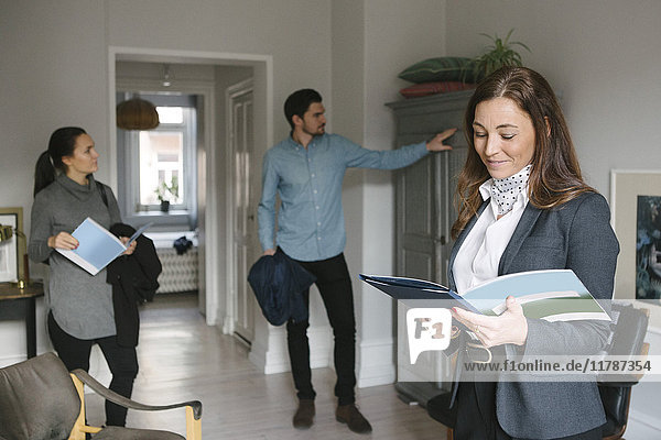 Lächelnde Immobilienmaklerin liest Broschüre  während das Paar zu Hause auf den Schrank schaut.
