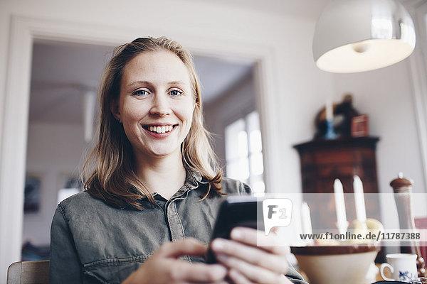 Niederwinkel-Porträt einer jungen Frau  die zu Hause mit dem Handy telefoniert