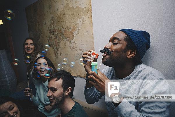 Junge Freunde sehen den Mann  der Blasen gegen die Wand im Schlafsaal bläst.