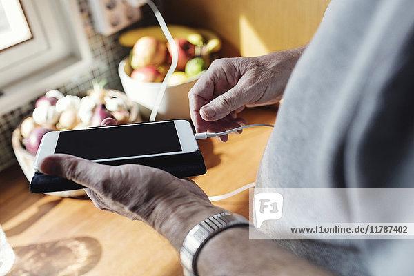 Abgeschnittenes Bild des Seniorenverbindungskabels zum Mobiltelefon am Küchenarbeitsplatz