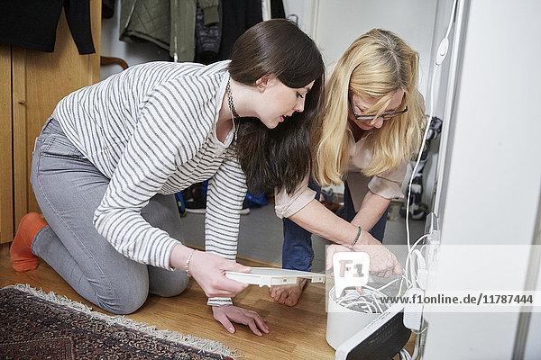 Mutter und Tochter prüfen zu Hause die Kabel an der Wand