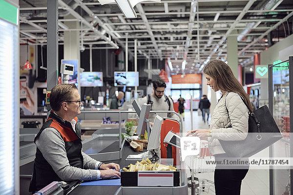 Reife Kassiererin betrachtet die Frau  die an der Kasse im Supermarkt durch Technologie zahlt.