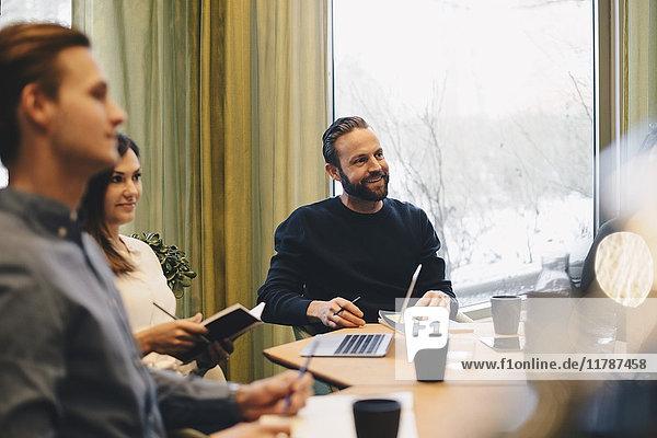 Geschäftsleute am Konferenztisch im hell erleuchteten Sitzungssaal