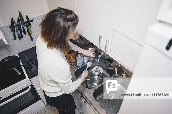 Hochwinkelansicht der Frau beim Geschirrspülen in der Küche im Wohnheim