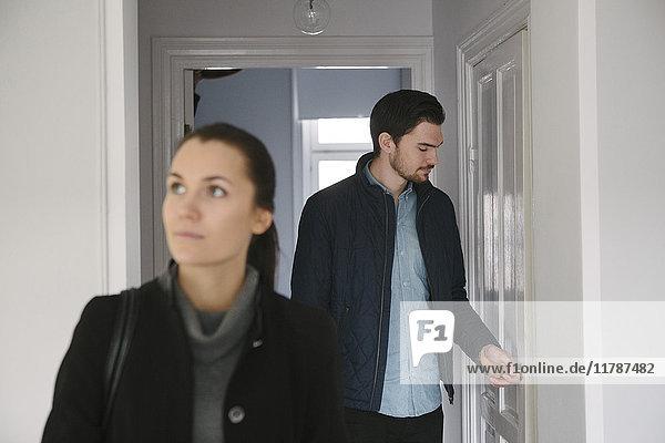 Junger Mann schaut auf die Tür  während er mit einer Frau im Flur steht.
