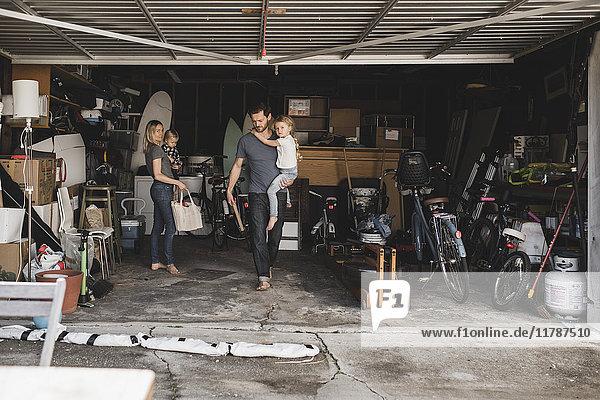 Mittlere erwachsene Eltern mit Kindern bei der Arbeit im Abstellraum in der Garage