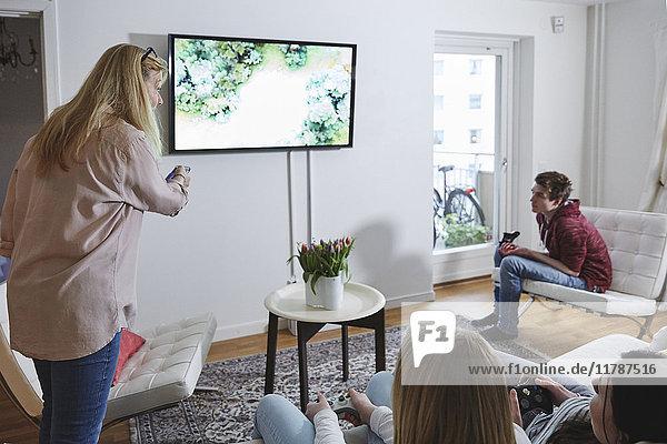 Mutter mit Fernbedienung  die Kinder beim Spielen von Videospielen im Wohnzimmer betrachtet