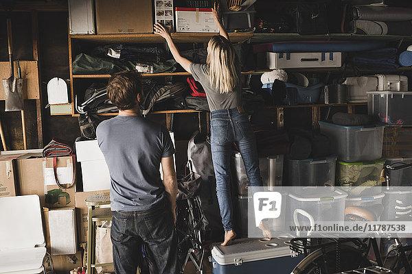 Rückansicht des Mannes mit Blick auf die Frau  die im Lagerraum Kisten anordnet.