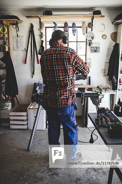 Durchgehende Rückansicht des in der Werkstatt arbeitenden älteren Mannes