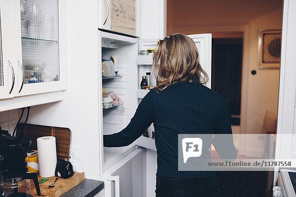 Rückansicht der Frau beim Öffnen des Kühlschranks in der heimischen Küche
