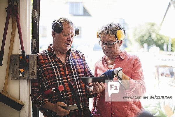 Seniorenpaar diskutiert über digitales Tablett beim Stehen vor der Werkstatttür