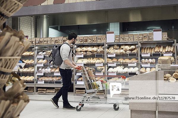 Seitenansicht des Mannes  der mit dem Wagen unterwegs ist  während er im Supermarkt das Brot betrachtet.