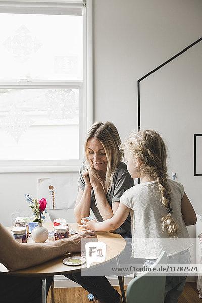 Tochter serviert Mutter Tee am Tisch im Spielzimmer