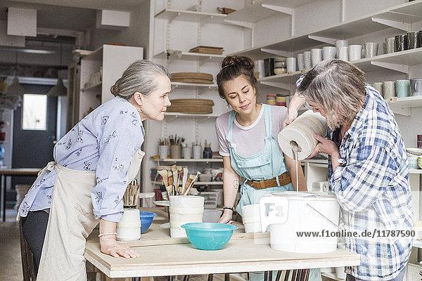 Senior Töpfer und junger Angestellter beim Anblick eines reifen Kollegen  der Ton aus einer Vase in einem Sieb auf einem Eimer in der Werkstatt gießt.