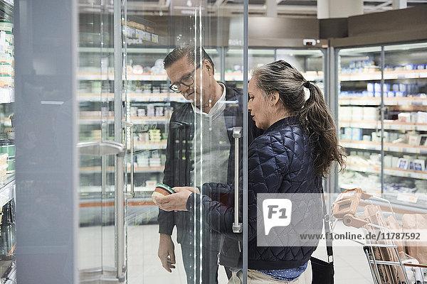 Paar betrachtet Lebensmittelbehälter im Kühlbereich des Supermarktes