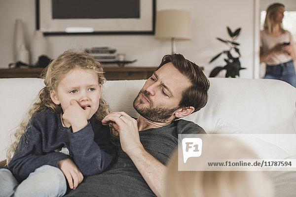 Mittlerer Erwachsener Mann  der die Tochter sieht  die zu Hause auf dem Sofa sitzt.