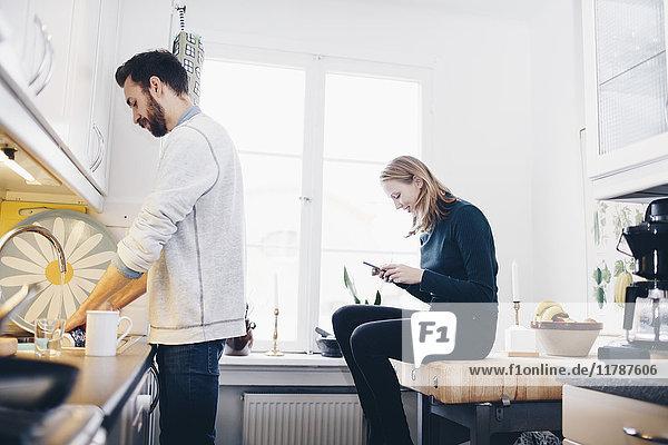 Seitenansicht des Mannes beim Geschirrspülen  während die Frau in der Küche zu Hause mit dem Handy telefoniert.