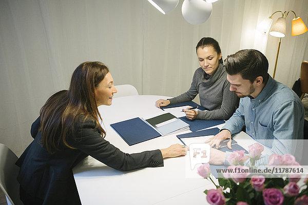 Hochansicht einer reifen Immobilienmaklerin  die dem jungen Paar mit einer Broschüre am Schreibtisch im Büro hilft