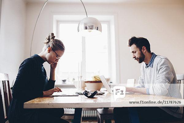 Seitenansicht des Paares mit Technologien am Esstisch bei der Arbeit von zu Hause aus
