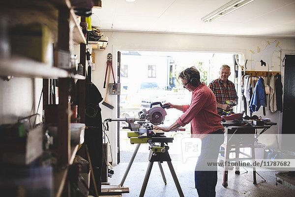 Seitenansicht der älteren Frau mit der Kreissäge  während der Mann im Hintergrund den Bohrer hält.