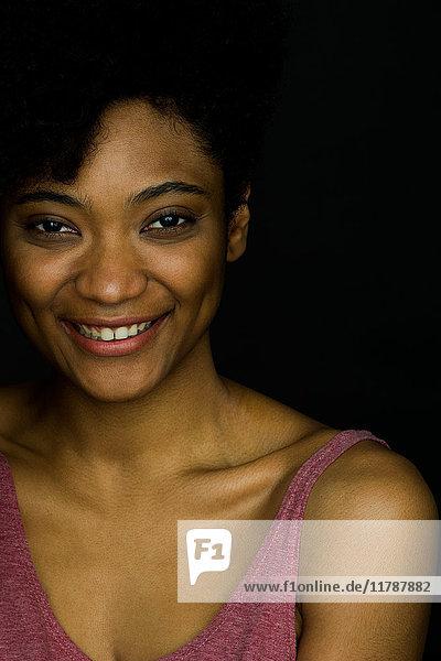 Junge Frau lächelt fröhlich mit der Hand im Haar  Portrait