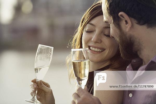 Pärchen feiern mit Champagner im Freien
