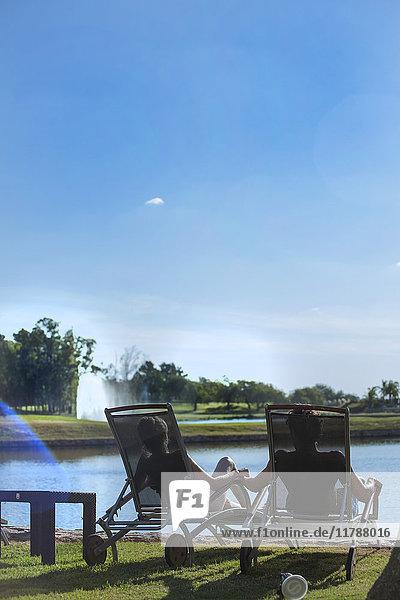 Paar entspannen in Liegestühlen am Ufer des Sees