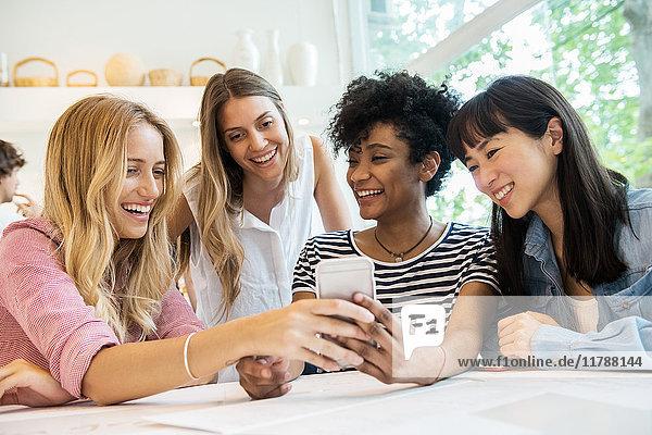 Freunde,  die das Smartphone gemeinsam im Cafe anschauen