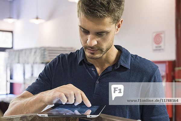 Mann mit digitalem Tablett in der Fabrik