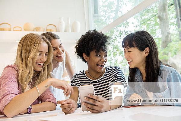 Junge Frauen  die Smartphones anschauen und gemeinsam lachen