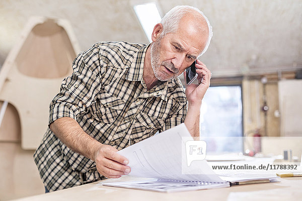 Senior Schreiner im Gespräch mit dem Handy und Überprüfung des Papierkrames in der Werkstatt