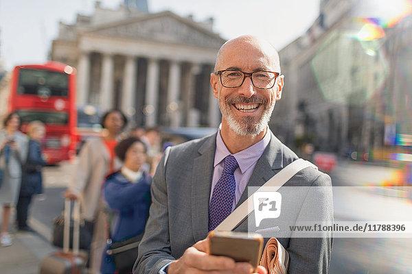 Portrait lächelnder  selbstbewusster Geschäftsmann mit Handy auf der urbanen City Street  London  UK