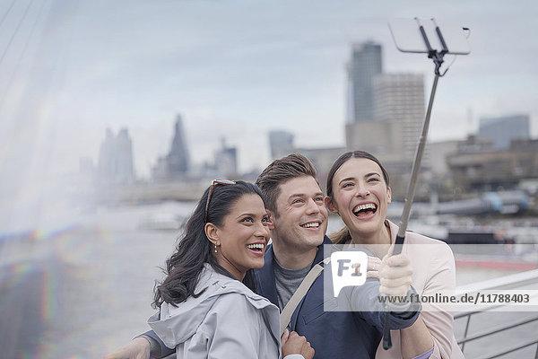 Enthusiastische, lächelnde Freund-Touristen, die Selfie mit Selfie-Stick auf urbaner Brücke nehmen, London, UK