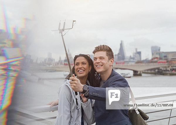 Paar Touristen  die Selfie mit Fotohandy Selfie Stick an der Themse River Waterfront  London  UK nehmen.