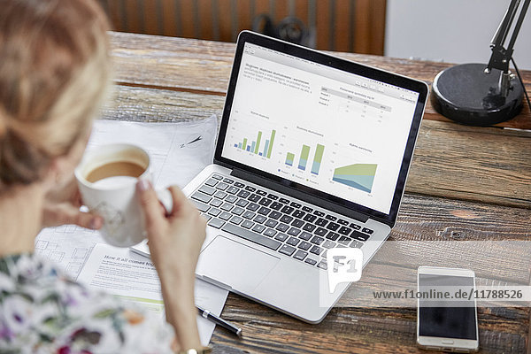 Geschäftsfrau trinkt Tee und überprüft Daten am Laptop