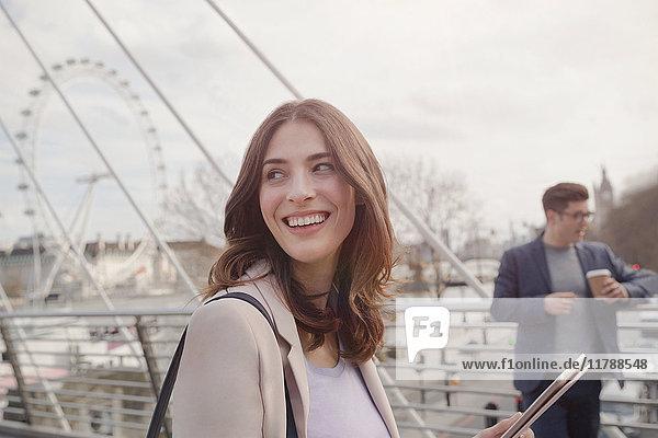 Lächelnde Frau auf der Stadtbrücke nahe Millennium Wheel, London, UK