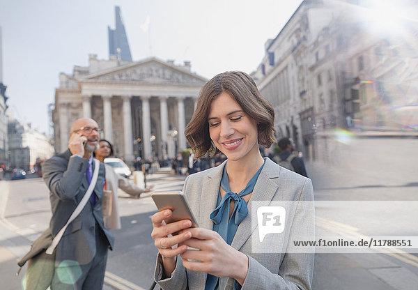 Geschäftsfrau SMS mit Handy in der City Street, London, UK
