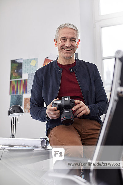 Portrait smiling  confident male photographer with digital camera in office