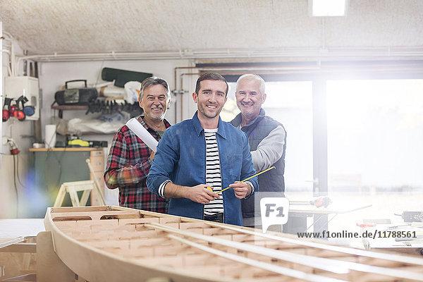 Portrait lächelnde Schreiner bei der Arbeit am Holzboot in der Werkstatt