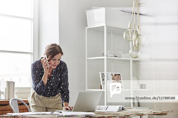 Geschäftsfrau beim Telefonieren und Arbeiten am Laptop im Büro