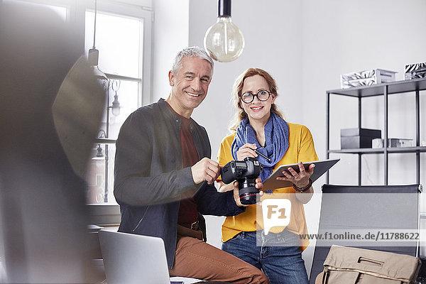 Portrait lächelnde  selbstbewusste Fotografen mit Digitalkamera und Digitaltablett im Büro