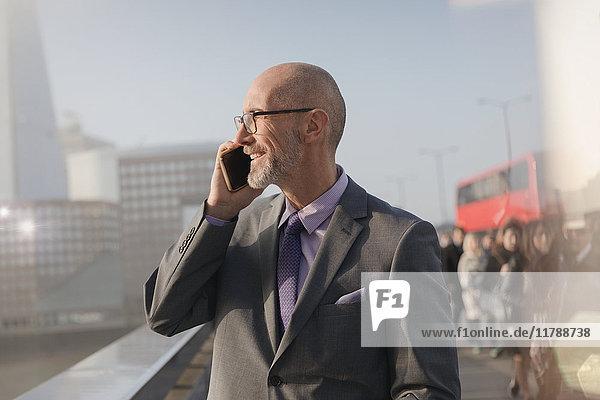 Geschäftsmann im Gespräch auf dem Handy auf der sonnigen Stadtbrücke  London  UK