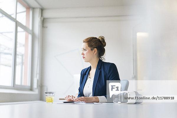 Geschäftsfrau am Schreibtisch mit VR-Brille