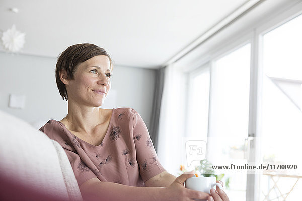 Porträt einer lächelnden Frau bei einer Tasse Kaffee zu Hause