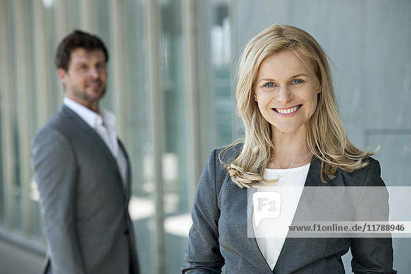Portrait of smiling businesswoman with her partner watching in the background