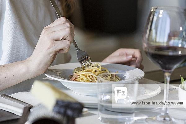 Frau isst Spaghetti Carbonara