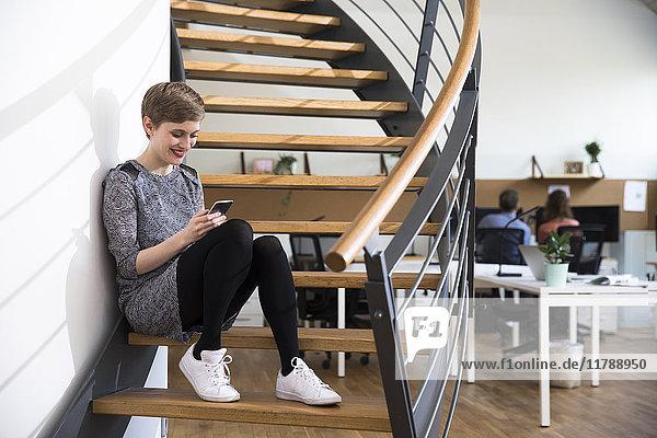 Lächelnde Frau auf der Treppe im modernen Büro mit Blick auf das Handy